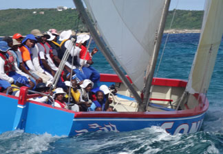 sonic crew up on the side of their boat during a tack