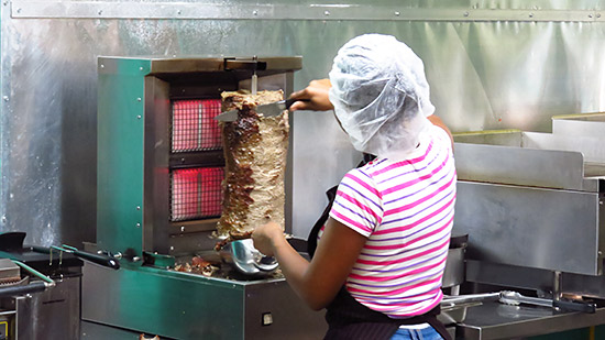 cutting the meat off the spit at zack shwarma
