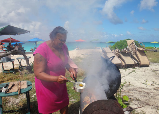 gwen buttering bbq lobster at her beach bar