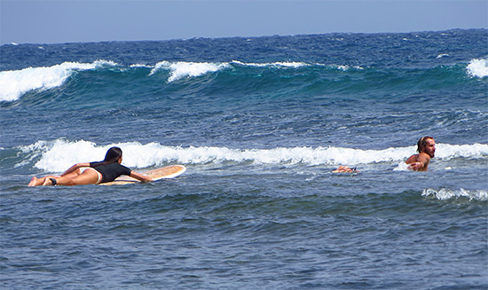 paddling out to surf in jobos puerto rico with rincon surf school