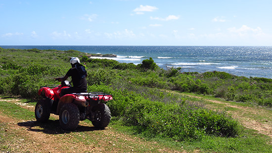 kirmani on freedom rentals atv with caribbean sea in the background