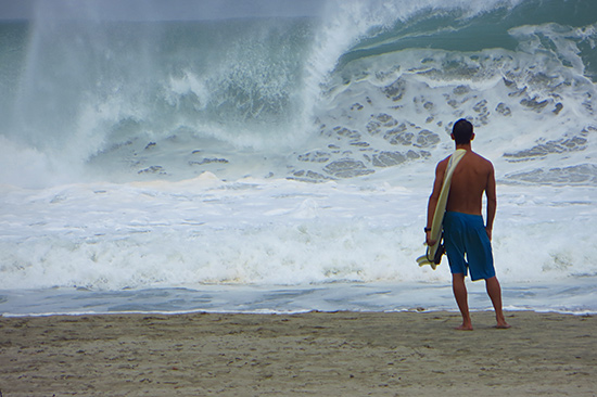 surfer watching the big waves at puerto escondido's main beach, zicatela
