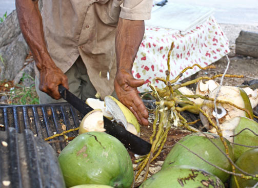 The coconut vendor slicing open a coconut