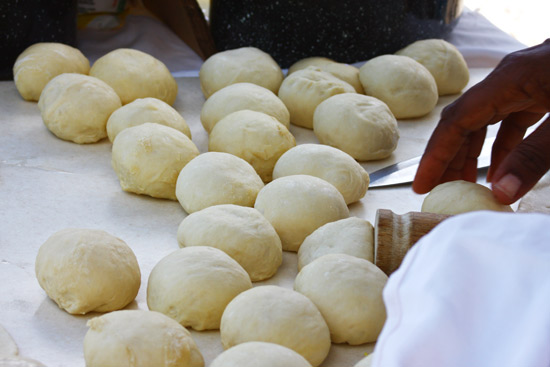 The rolling up of the dough to make Johnny Cakes