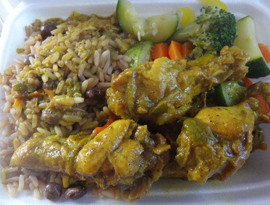curry chicken wings with rice and peas and vegetables