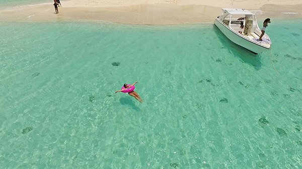 floating in the water around sandy island
