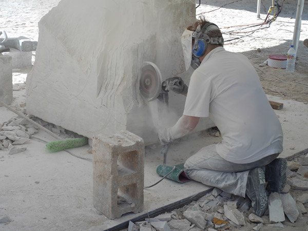 grinding stone into sculpture in anguilla