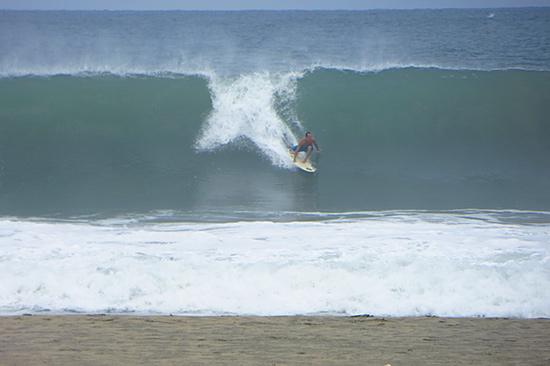 surfer watching the big waves at puerto escondido's main beach, zicatela